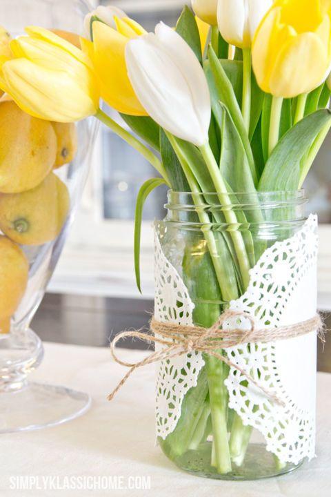 Mesa de cumpleaños con tulipanes en jarros de cristal